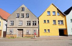 Restauriertes Wohnhaus mit gelb gestrichener Fassade, verfallenes Gebäude mit abbröckelndem Putz und Luken verschlossene Fenster; Architekturbilder aus Barth / Alt + Neu.