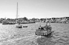 Hafen von Vitte auf der Insel Hiddensee, Mecklenburg Vorpommern. Ein Fischkutter fährt zu seinem Liegeplatz - ein Segelboot fährt unter Motor zum Kai.