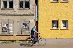 Restauriertes Wohnhaus mit gelb gestrichener Fassade, verfallenes Gebäude mit abbröckelndem Putz und Luken verschlossene Fenster - Fahrradfahrer; Architekturbilder aus Barth  / Alt + Neu.