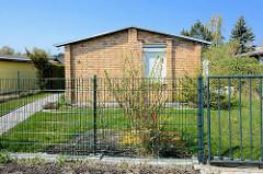 Einraum / Einzimmer Ferienhaus - Fassade mit Ziegelsteinen verkleidet, Vorgarten mit hohem Metallzaun; Zingst, Mecklenburg-Vorpommern.