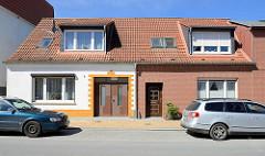 Doppelhaus mit unterschiedlich gestalteter Fassade, Nördlicher Rosengarten / Ribnitz-Damgarten; weisse Hausfassade mit gelb abgesetztem Eingang / Ausfahrt - Ziegelfassade.