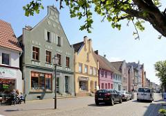 Geschäftsstraße in der Innenstadt von Barth / Lange Straße - Wohnhäuser / Geschäftshäuser mit Geschäften im Erdgeschoss - Fassaden mit Scheingiebel, unterschiedliche Farbigkeit.