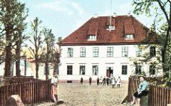 Das alte Hannoversche Amtshaus Wilhelmsburg wurde 1724 auf den Grundmauern der Grotenburg errichtet. 1865 wird das Gebäude verkauft und als Kirchdorfer Schule genutzt. Kinder kommen aus dem Gebäude und stehen auf dem Schulhof.