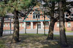 Verwaltungsgebäude, Rathaus der Gemeinde Zingst - Blick durch Kiefern, Fachwerkarchitektur im Heimatstil.
