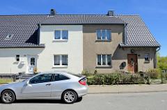 Schlichtes einstöckiges Wohnhaus, symmetrisch mittig geteilt, grauer Rauhputz und weiße Hausfassade  - Klüßenberg in Ribnitz-Damgarten.