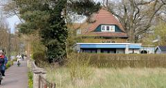 Flachdach-Ferienhaus mit abgeschrägter Wand / Terrasse hinter hoher Hecke; dahinter hohes Wohnhaus mit Dachfenster; Ostseebad Zingst, Mecklenburg-Vorpommern.