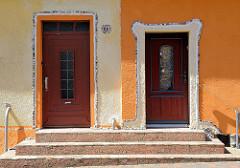Hauseingänge in der Mühlenstraße von Ribnitz-Damgarten; farblich mittig geteilt, gelb + orange - Mosaik Verzierung.