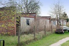 Verlassene Ferienhaussiedlung, leere verfallene Ferienhäuser; eingeschlagene Fensterscheiben - Zingst, Mecklenburg-Vorpommern.