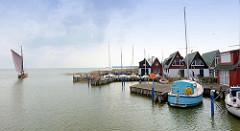 Ferienhäuser am Wasser, Hafen von Altenhagen / Ostseebad Ahrenshoop. Ein Zeesenboot fährt in den Saaler Bodden. Das Zeesenboot ist ein Fischerboot und hat einen geringen Tiefgang - so ist es sehr gut geeignet für das Fischen in den flachen Küsten- un