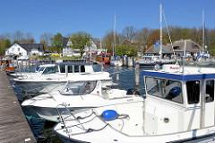 Hafenanlage von Kloster auf der Ostseeinsel Hiddensee - Motorboote liegen am Steg, im Hintergrund das reetgedeckte Gebäude des  Hafenmeisters.