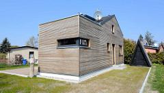 Modernes Wochenendhaus, Wohnhaus mit Holzfassade und Spitzdachschuppen - re. im Hintergrund einfaches Ferienhaus mit Rauputz - Ostseebad Zingst, Mecklenburg-Vorpommern.