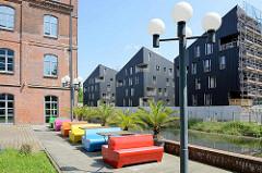 Altbauten / Neubauten, moderne und historische Architektur am Kaufhauskanal in Hamburg Harburg -  Wohnquartier Maritimes Wohnen; bunte Plastikbänke an der Kanal Promenade.