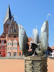 Marktbrunnen am Marktplatz der Stadt Barth - Wasserspeier Fische / Entwurf Bauhausschüler Wilhelm Löber, errichtet 1958. Im Hintergrund die Barther St. Marienkirche.