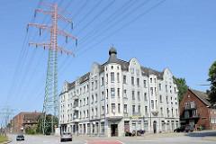 Jugendstil Wohnblock / Eckgebäude an der Seehafenstraße / 1. Hafenstraße in Hamburg Harburg; hoher Strommast / Freileitungsmast -  eine 380 KV Stromleitung / Hochspannungsleitung verläuft über dem Wohngebäude.