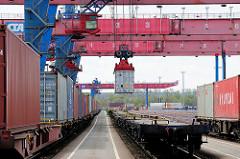 Die Ladung eines Containerzugs wird im Containerbahnhof Hamburg Altenwerder gelöscht - einer der Container wird mit einem Portalkran vom Güterwaggon zum Sattelauflieger transportiert.