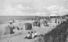 Historisches Motiv vom  Ostseebad Zingst - Sandburgen mit Strandkörben, Badegäste am Strand; im Hintergrund die Seebrücke.