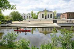 Blick über die Rathauswettern zur Industriearchitektur vom ehem. Wasserwerk in Hamburg Wilhelmsburg - Fahrräder auf der Promenade, ein Kanu fährt auf dem Entwässerungsgraben.