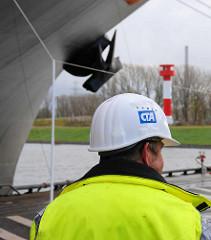 Ein Arbeiter auf dem Terminal Altenwerder - er trägt einen Schutzhelm mit dem Emblem des CTA und eine Arbeitsjacke in Signalfarben; im Hintergrund ein Schiffsbug mit Anker und ein Leuchtturm.
