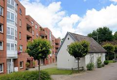 Wohnblock / Neubau und historisches Deputatshaus an der Dorfstraße in Glinde - in den 1970er Jahren konnte der Abriss der alten Häuser verhindert werden. Deputatshäuser wurden Landarbeitern für einen Teil ihres Lohns zur Verfügung gestellt.