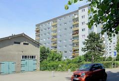 Schuppen / Garage mit grauer Putzfassade - Hochhaus / Wohnsiedlung in Wentorf bei Hamburg.