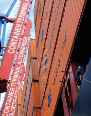 """Die Containerbrücken sind hoch geklappt, die Beladung des Containerschiffs ist beendet - die Ausleger der Containerbrücke sind mit dem Schriftzug """"Container Terminal Altenwerder"""" versehen."""