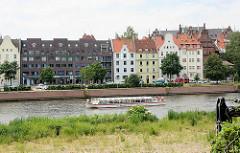 Ausflugsschiff fährt mit Touristen auf der Kanaltrave von Lübeck.
