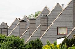 Mit Schindeln verkleidete Schornsteine und Hausfassaden - Doppelhäuser in der Straße Blöcken in Barsbüttel.