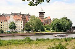 Turm vom spätgotisches Burgtor - Wohnhäuser, ein Ausflugsschiff fährt mit Touristen auf der Kanaltrave von Lübeck.