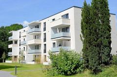 Weißer, kubischer Wohnblock mit teilweise überdachten Balkons - Architektur in Wentorf bei Hamburg.