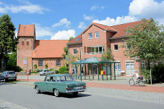 Am Markt von Sülfeld - historische Sülfelder Kirche - schlichter Neubau, Bushaltestelle mit Metall-Wartehäuschen.