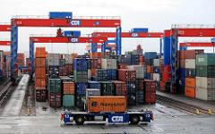 Containertransport auf dem Hamburger Containerterminal Altenwerder - im Vordergrund transportiert ein automatisches Fahrzeug (Automated guided Vehicles / AGV ) einen Container.