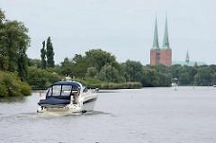 Ein Sportboot fährt auf der Kanaltrave Richtung Lübeck - im Hintergrund die Türme vom Lübecker Dom.