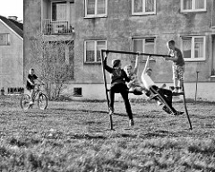 Spielende Kinder an der Teppichstange - Wohnblock mit Rauhputz, Woiwodschaft Ermland-Masuren in Polen.