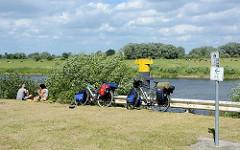 Fahrradtour - Rast an der Elbe bei Bleckede; hoch bepackte Fahrräder / Fahrradtaschen - Picknick am Wasser.