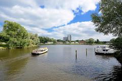 Blick vom Stadtgraben / Alte Trave auf die Kanaltrave in Lübeck. Ein Ausflugsschiff fährt in den Kanal ein.