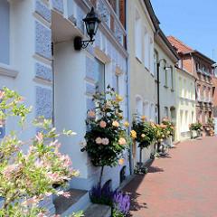 Straße in Mölln - Hauseingänge mit blühende Rosen / Stockrosen bepflanzt.