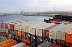 """Container an Deck des Containerschiffs """"Hanover"""" an den Kaianlagen des Terminals Altenwerder; im Hintergrund die Kattwyckbrücke und Windräder zur Energiegewinnung."""