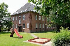Kasernengebäude der 1936/37 errichteten Bismarck Kaserne in Wentorf bei Hamburg; jetzt Wohnnutzung - Kinderspielplatz mit Rutsche und Sandkasten / Rasen.