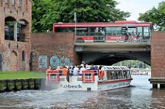 Brücke über die Trave beim Holstentorplatz in Lübeck - ein Ausflugsschiff mit Touristen durchfährt den Brückenbogen - oben ein Autobus.