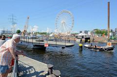 Die Drehbrücke / Fussgängerbrücke über den Lotsenkanal im Harburger Binnenhafen ist geöffnet; ein Festmacherboot passiert die Durchfahrt..
