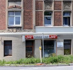 Jugendstilwohnblock / Eckgebäude in Hamburg Wilhelmsburg; Restbestand von im Krieg zerbombten Wohnbebauung. Erdgeschoss Fassade mit gelben Kacheln versehen - Ladenlokal, Frühstück.