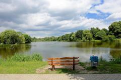 Blick auf den Mühlenteich / Glinder Au - Bäume am Wasser, blauer Himmel - weisse Wolken / Holzbank, Ruhebank am Ufer des Sees.