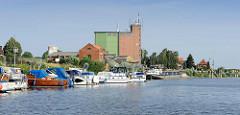 Hafen von Bleckede an der Elbe; Sportboote in der Marina, ein Binnenschiff liegt am Hafenkai. Speichergebäude / Silo und Wohnhäuser am Hafenrand.
