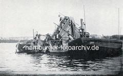 Historische Aufnahme eines Dampfbaggers / Ketteneimerbaggers auf der Hamburger Aussenalster - das Baggergut wird in eine längsseits liegende Schute gefüllt.