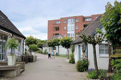 Wohnblock / Neubau und historische Deputatshäuser an der Dorfstraße in Glinde - in den 1970er Jahren konnte der Abriss der alten Häuser verhindert werden. Deputatshäuser wurden Landarbeitern für einen Teil ihres Lohns zur Verfügung gestellt.