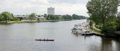 Blick vom Stadtgraben / Alte Trave auf die Kanaltrave in Lübeck. Im Hintergrund der 1954 gebaute 70 m hohe Gasometer / Scheibengasbehälter
