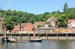 Werftkai an der Elbe / Mündung vom Elbe-Lübeck-Kanal in Lauenburg, Arbeitsschiffe und Werftkran; am Ufer Wohnhäuser.