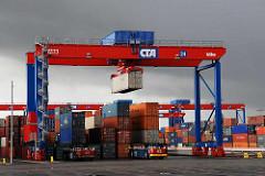 Ein Containerkran / Portalkran transportiert einen Container auf dem Terminalgelände Hamburg Altenwerder.