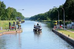 Witzeezeschleuse am Elbe-Lübeck-Kanal, die Schleusentore sind geöffnet, ein Motorboot fährt in den Kanal ein.