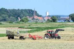 Heuernte an der Elbe - die Heuballen werden von Hand auf dem Anhänger verstaut; im Hintergrund Kirchturm und Häuser von Lauenburg.